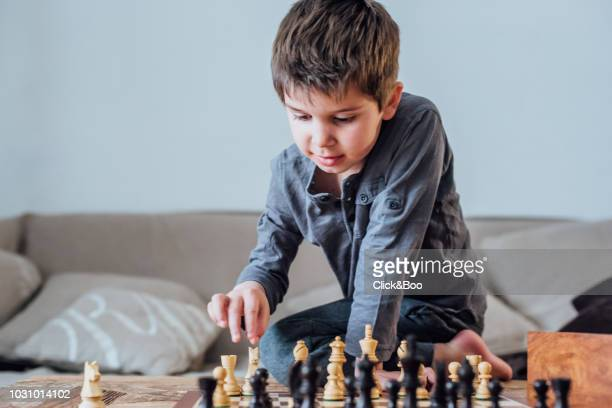 Little boy playing chess indoors (home interior)