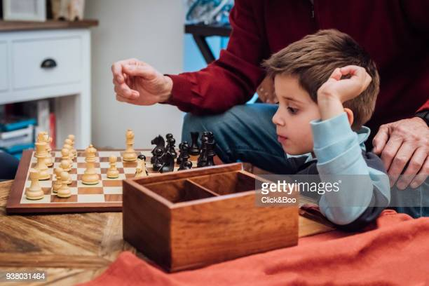 Little boy playing chess with grandfather