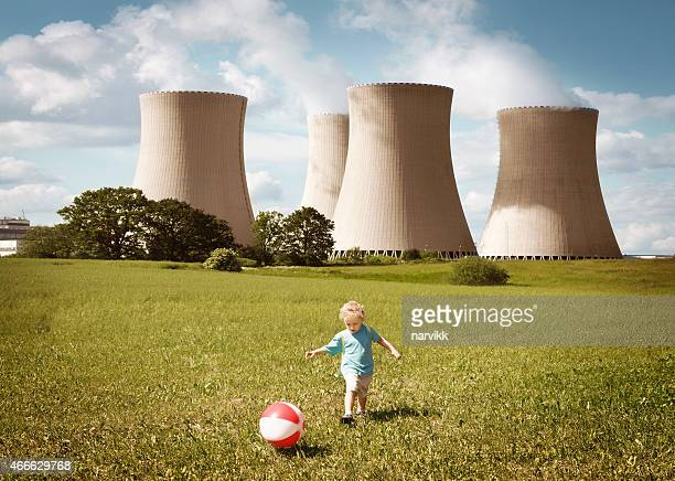 Little boy playing close to the nuclear plant