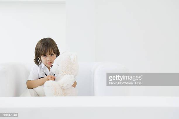 Little boy playing doctor with teddy bear, using stethoscope