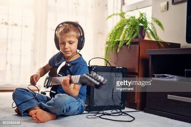 little boy playing electric guitar - electric guitar stock pictures, royalty-free photos & images