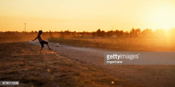 Little boy playing football on dirt road