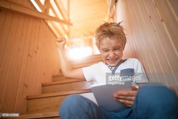 Little boy playing game on a digital tablet