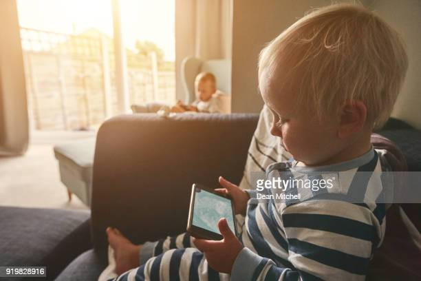 Little boy playing games on mobile phone at home