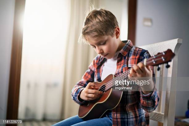 little boy playing guitar at home - ukulele stock pictures, royalty-free photos & images