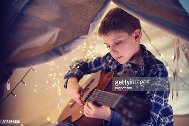 Little boy playing guitar in his teepee tent