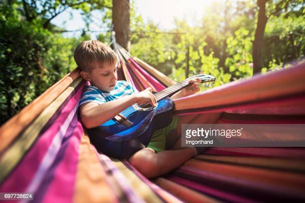 little boy playing guitar on hammock - lazy poland stock photos and pictures