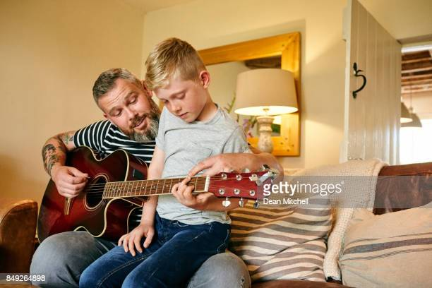 Little boy playing guitar with his father