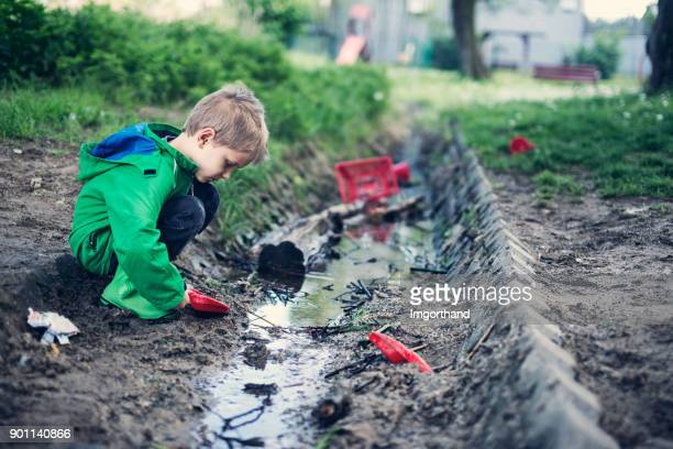 Little boy playing in a dirty mud full of waste