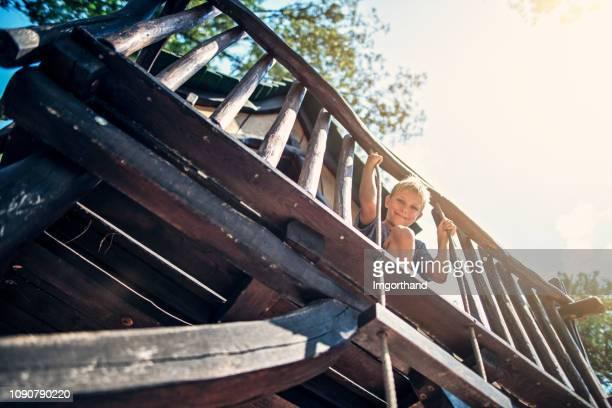 木の家で遊ぶ少年 - 掘建て小屋 ストックフォトと画像