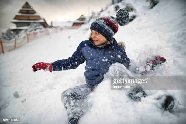 Little boy playing in fresh snow