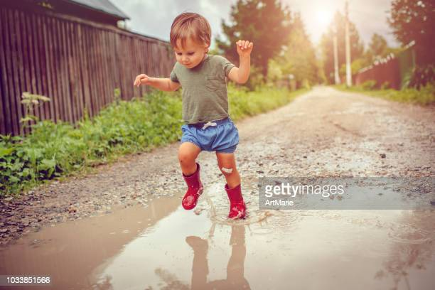 little boy playing in puddle - toddler stock pictures, royalty-free photos & images