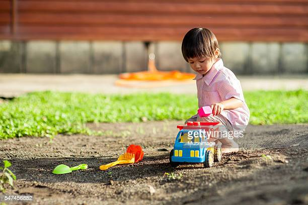Little Boy Playing In Sandbox
