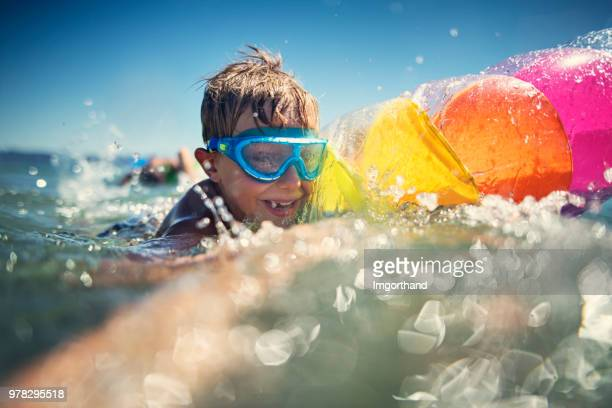 Little boy playing in sea with air mattress