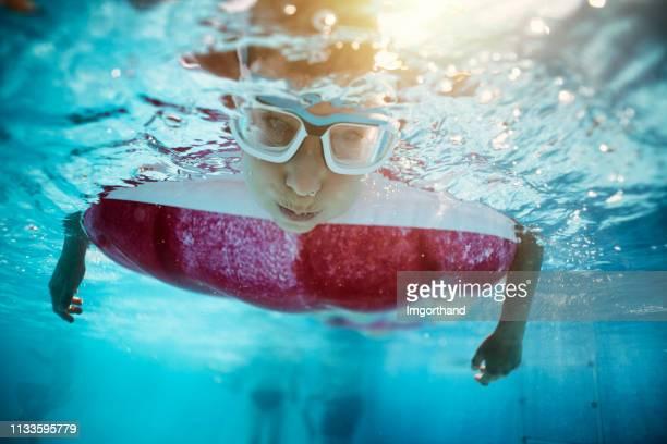 スイミングプールで遊んでいる小さな男の子は、空気ベッドから水中見て - 息を止める ストックフォトと画像