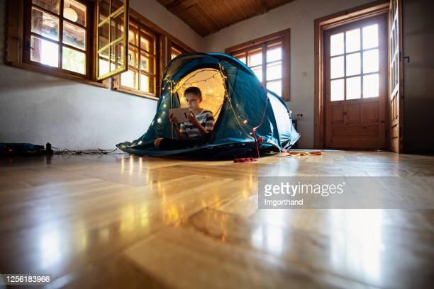 小男孩在客廳的帳篷里玩耍 - 跟拍鏡頭 個照片及圖片檔