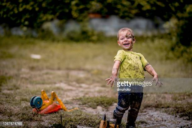 little boy playing in the mud. - gold shoe stock pictures, royalty-free photos & images