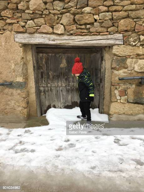 Little boy playing in the street covered with snow