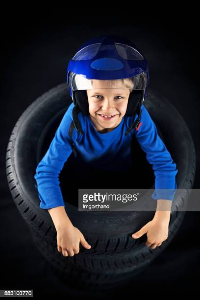 Little boy playing in tyres