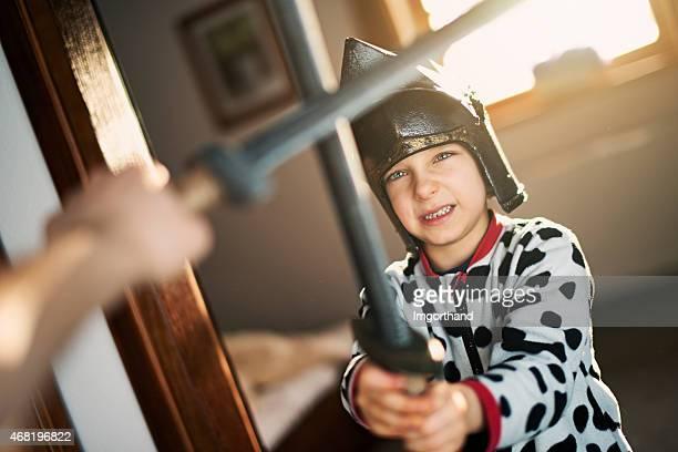 Kleine Jungen spielen und kämpfen knight