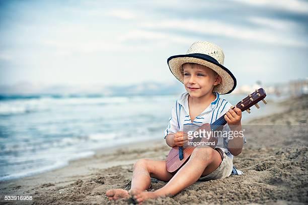 Little boy playing little guitar on the beach.