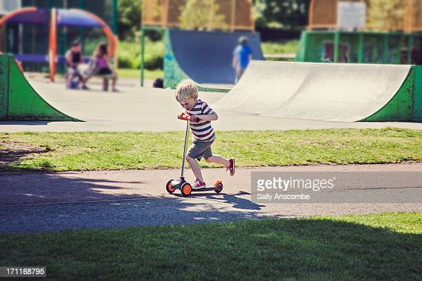 Little boy playing on a scooter in the park