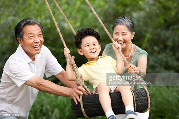 Little boy playing on a swing with grandparents