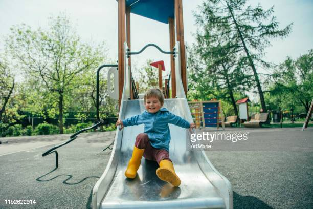 little boy playing on playground in summer - slide play equipment stock pictures, royalty-free photos & images