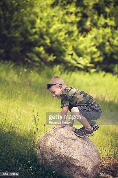 Little boy playing on rock