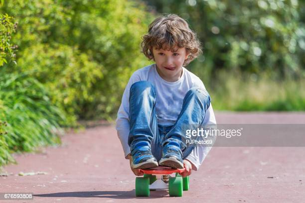 Little boy (6 years) playing on skateboard