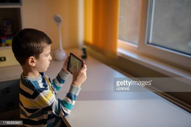 little boy playing on tablet - palm sunday photos et images de collection