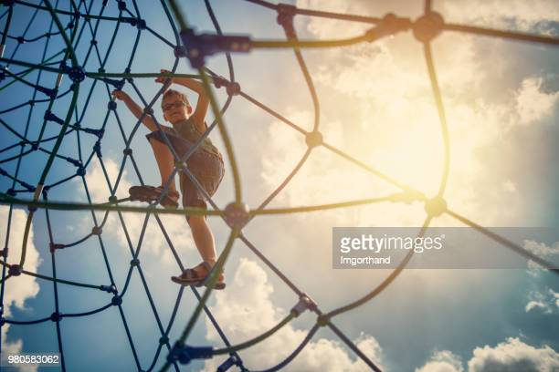 Little boy playing on the playground climbing web