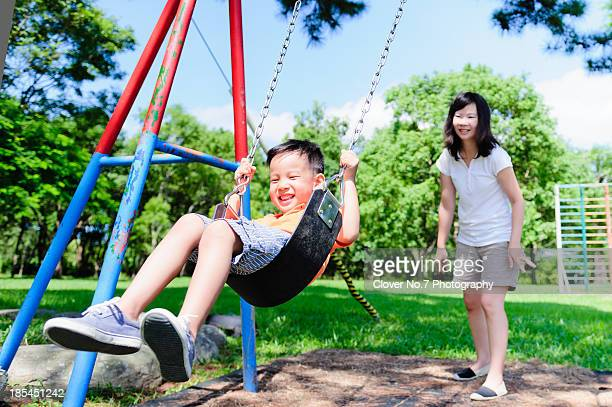 Little boy playing on the swings