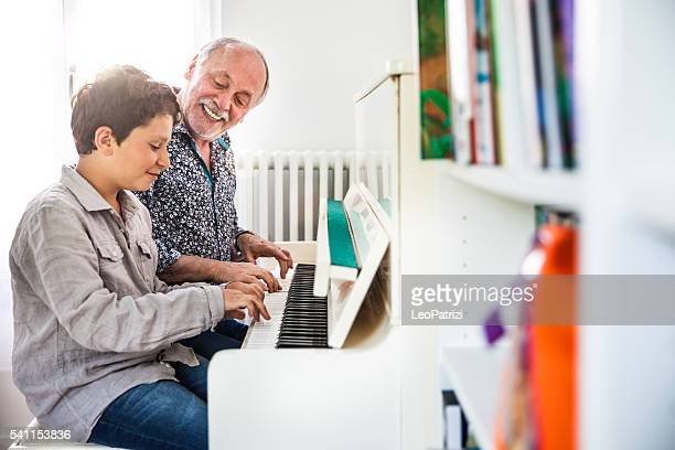 Little boy playing piano with his grandfather