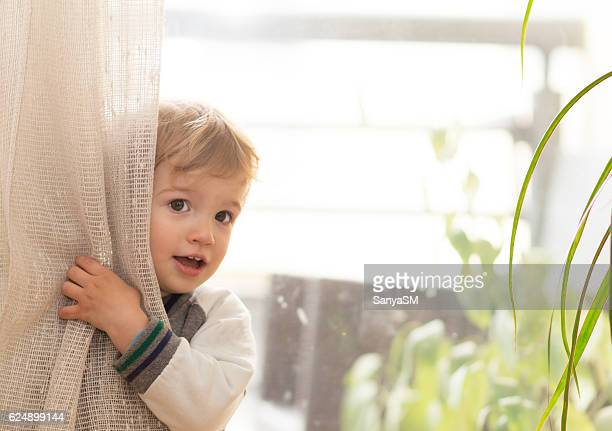 Little boy playing seek and peek