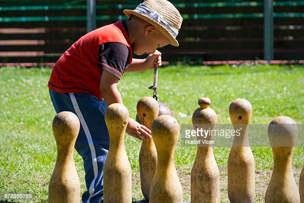 Little boy playing skittles, sunny day, outdoors
