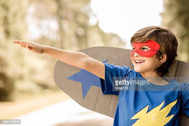 Little boy playing superhero outdoors.