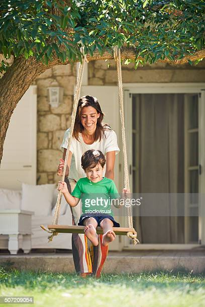 Little boy playing swing with mother