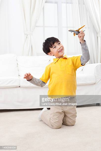 Little boy playing toy plane