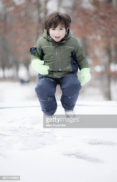 Little boy playing under the snowfall