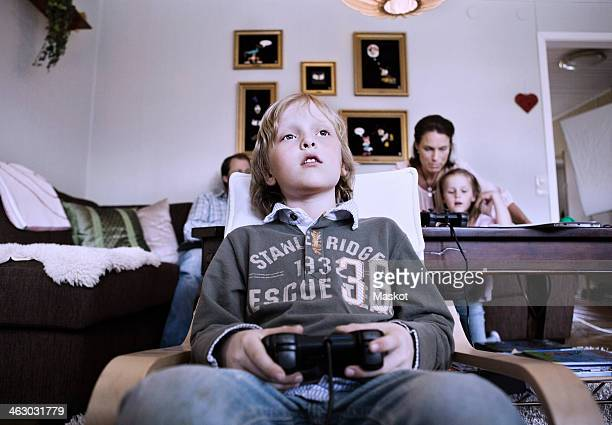 Little boy playing video game at home with family in background