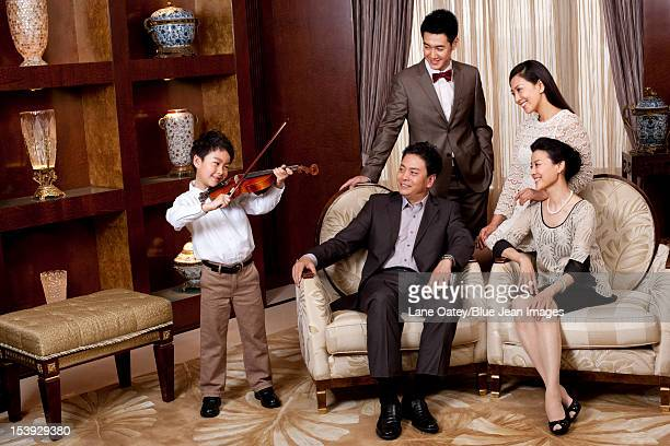 Little boy playing violin in front of family members