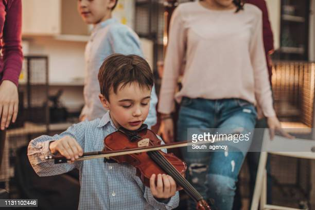 little boy playing violin - violin family stock photos and pictures