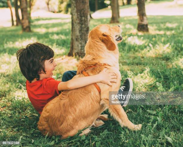 Little boy playing with a dog