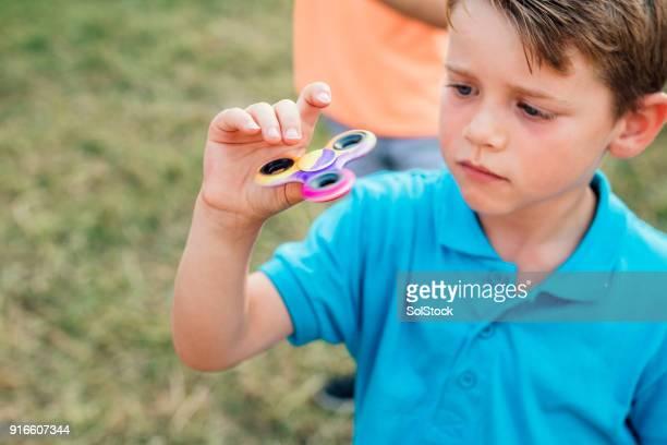 Kleiner Junge spielt mit einem Fidget Spinner