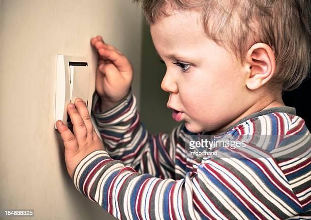 Little boy playing with a light switch.