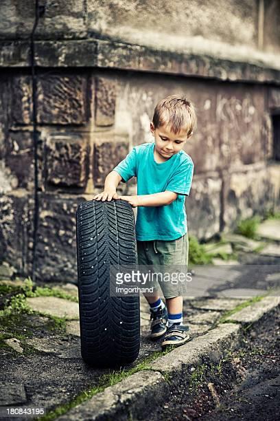 Rapaz brincando com um pneu