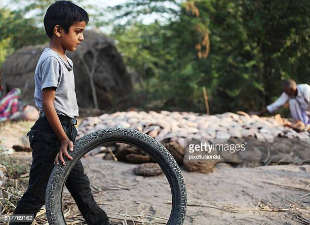 little boy playing with a tire. - indian slums stock pictures, royalty-free photos & images