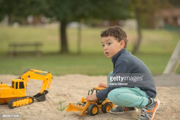 A little boy playing with a yellow backhoe outside