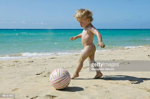little boy playing with ball on beach